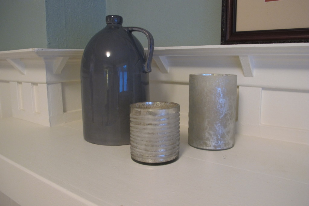 A jug and some metallic votive holders.