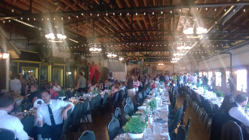 {The wedding was at the Kellerman Event Center. This photo is horrible, but the venue was beautiful with exposed beams and dark wood ceilings and floors. I loved the long tables.}