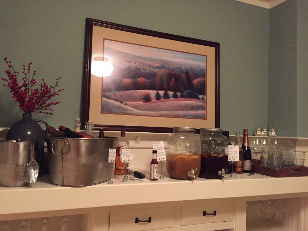 {Alex was in charge of drinks. We had a big batch of Maple Bourbon Splash and another dispenser with Cranberry Lime Spritzer, along with red wine, beer, homemade Irish cream and egg nog.}