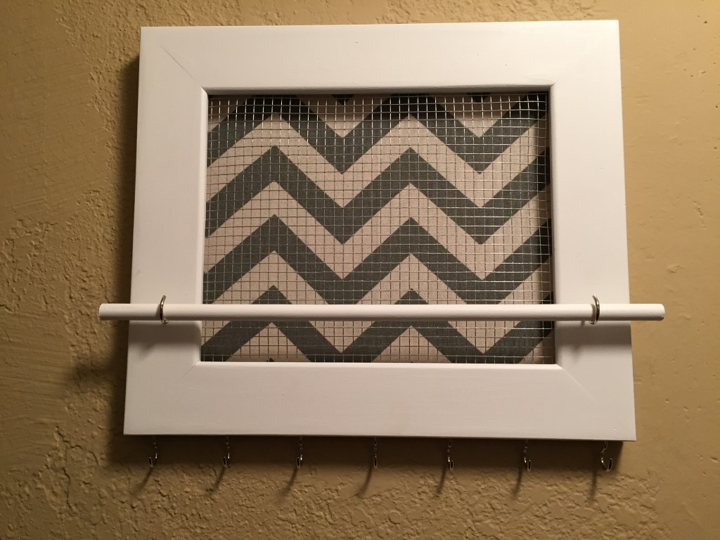 {this is the jewelry organizer without anything on it - the hooks below the frame are to hang necklaces, while the rod is to hang bracelets. If you look closely you can see some chicken wire on the outside of the chevron - that's earring storage!}
