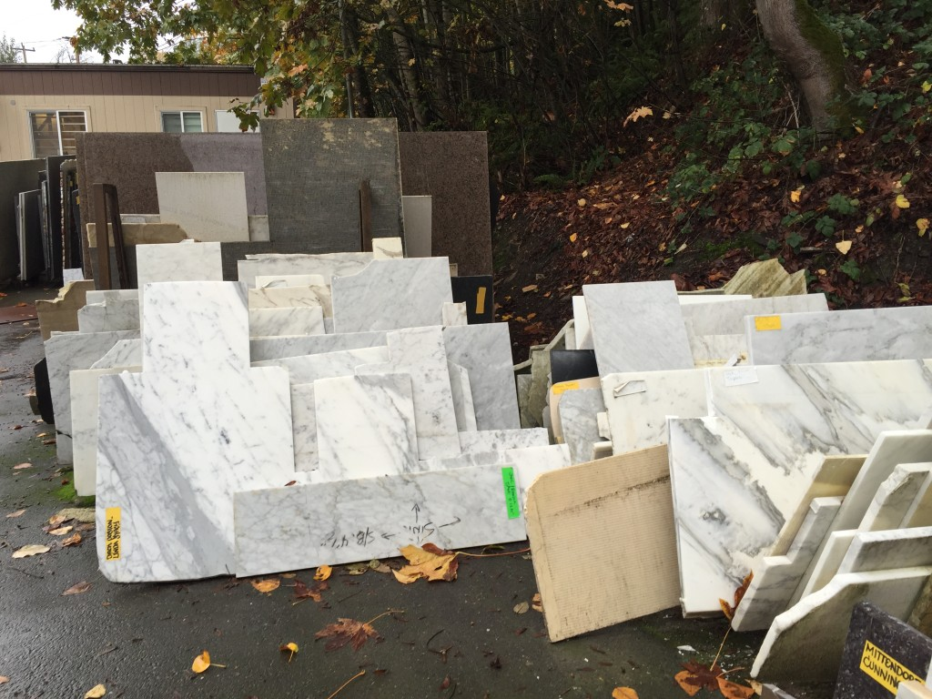 """{on Monday I had to make a trip to the slab """"graveyard"""" and pick out a large-ish slab of marble to be used for the threshold into the bathroom, as well as the curb getting into the shower, the shelving in the built-in storage niches and the window sill. the contractor advised this so that all of those surfaces would be the same look, since marble can appear very different. It was an undertaking since all of the slabs in this photo were stacked up next to each other and they were not easy to handle.}"""